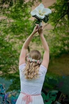 Flacher fokus einer jungen blonden braut, die einen blumenstrauß in einem park wirft