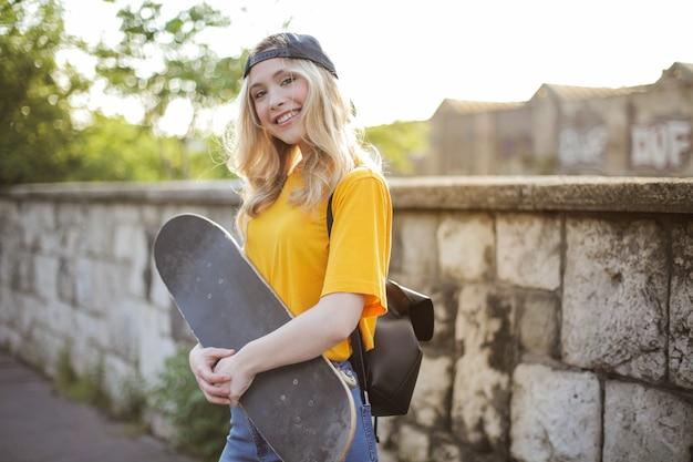 Flacher fokus einer jungen lächelnden blonden frau mit einem skateboard posiert in einem par