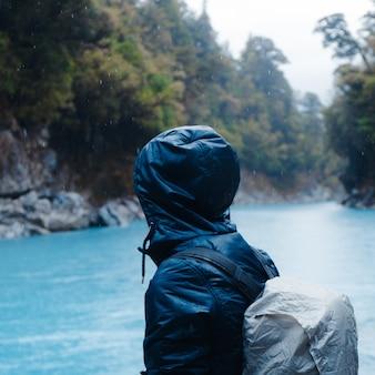 Flacher fokus einer person, die einen regenmantel mit einem rucksack trägt, der während des regens von bäumen umgeben ist