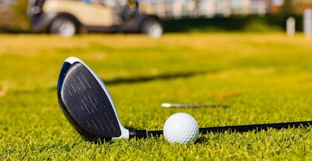 Flacher fokus eines golfschlägers und eines balls auf einer wiese