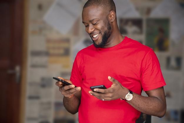 Flacher fokus eines jungen afrikanischen mannes, der zwei telefone in einem raum benutzt