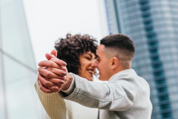 Flacher fokus eines jungen romantischen paares, das draußen tanzt und küsst