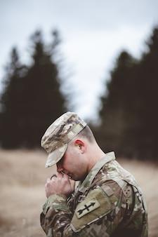 Flacher fokus vertikaler schuss eines jungen soldaten, der in einem feld betet
