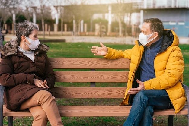 Flacher fokus von zwei erwachsenen menschen mit gesichtsmasken, die getrennt auf einer bank sitzen und plaudern