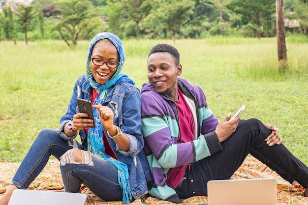 Flacher fokus von zwei jungen leuten in einem park, die sich gegenseitig inhalte auf ihren handys zeigen