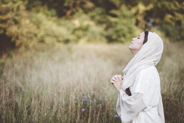 Flacher fokusschuss der frau, die eine biblische robe trägt, die mit ihrem kopf in richtung himmel betet