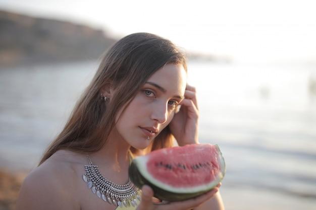 Flacher fokusschuss einer attraktiven frau, die eine melone hält, während sie die kamera betrachtet