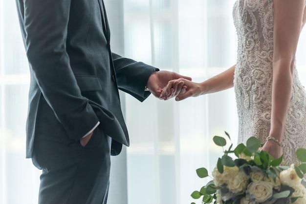 Flacher fokusschuss einer braut und eines bräutigams, die hände miteinander halten