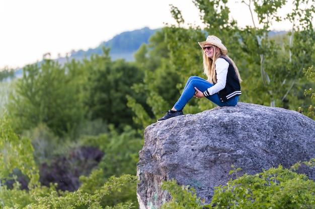 Flacher fokusschuss einer europäischen frau mit cowboyhut, die auf einem felsen in der natur sitzt