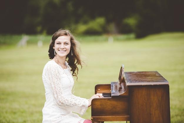 Flacher fokusschuss einer frau, die das klavier spielt, während sie in die kamera lächelt