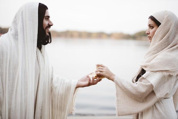 Flacher fokusschuss einer frau, die ein biblisches gewand trägt und das brot aus der hand jesu christi greift