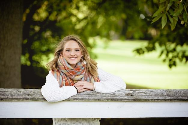 Flacher fokusschuss einer frau mit ihren händen auf dem zaun, während sie in die kamera lächelt