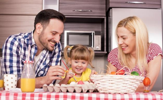 Flacher fokusschuss einer glücklichen familie, die ostereier in der freude malt