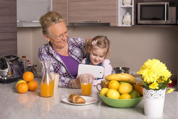 Flacher fokusschuss einer großmutter, die mit ihrem enkelkind auf das smartphone schaut