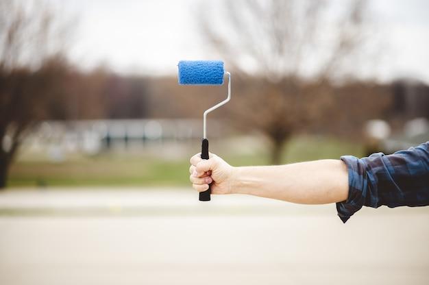 Flacher fokusschuss einer hand, die einen blauen pintpinsel mit einem park hält