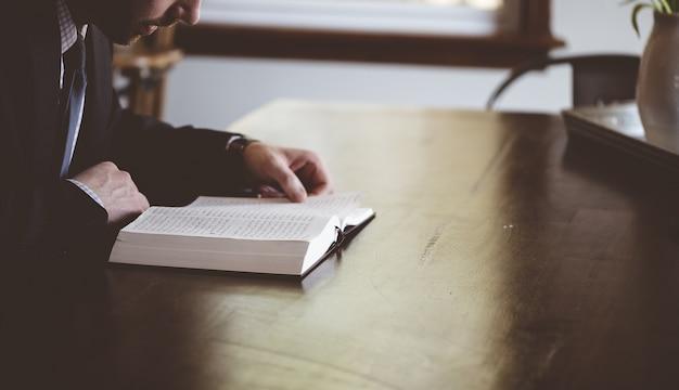 Flacher fokusschuss einer person, die ein arabisches buch liest