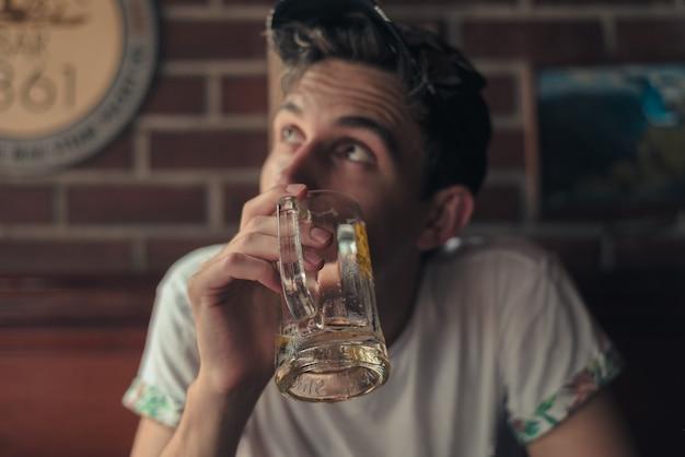 Flacher fokusschuss einer person, die ein leeres bierglas hochhält
