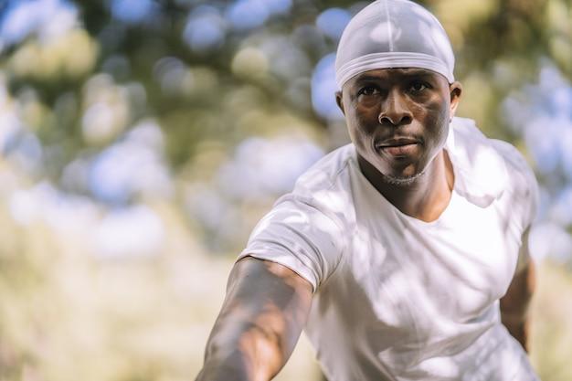Flacher fokusschuss eines afroamerikanischen mannes in einem weißen hemd, das sich am park ausdehnt