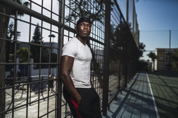 Flacher fokusschuss eines afroamerikanischen mannes in einem weißen hemd, das sich auf einen zaun stützt