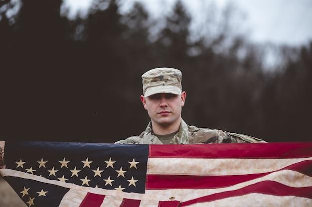 Flacher fokusschuss eines amerikanischen soldaten, der die amerikanische flagge hält