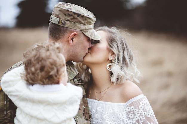 Flacher fokusschuss eines amerikanischen soldaten, der sein kind trägt, während er seine liebende frau küsst