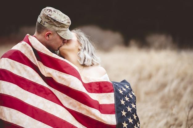 Flacher fokusschuss eines amerikanischen soldaten, der seine liebende frau küsst, während er in eine amerikanische flagge gehüllt wird