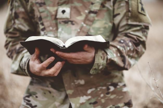 Flacher fokusschuss eines jungen soldaten, der eine offene bibel in einem feld hält