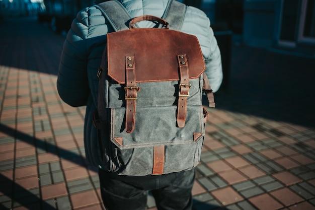 Flacher fokusschuss eines mannes, der einen grauen und braunen rucksack trägt