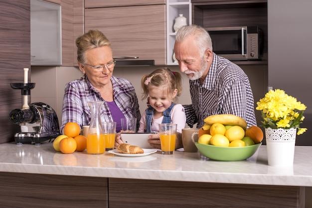 Flacher fokusschuss von großeltern, die das smartphone mit ihrem enkelkind betrachten