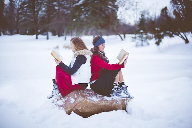 Flacher fokusschuss von zwei frauen, die rücken an rücken auf dem felsen sitzen, während sie die bibel lesen