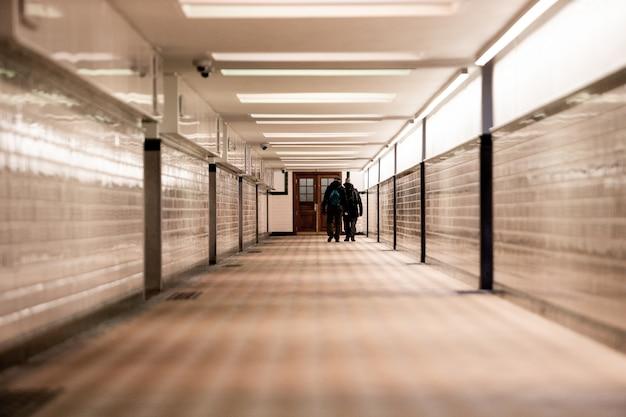 Flacher fokusschuss von zwei männern, die entlang eines hellen korridors gehen