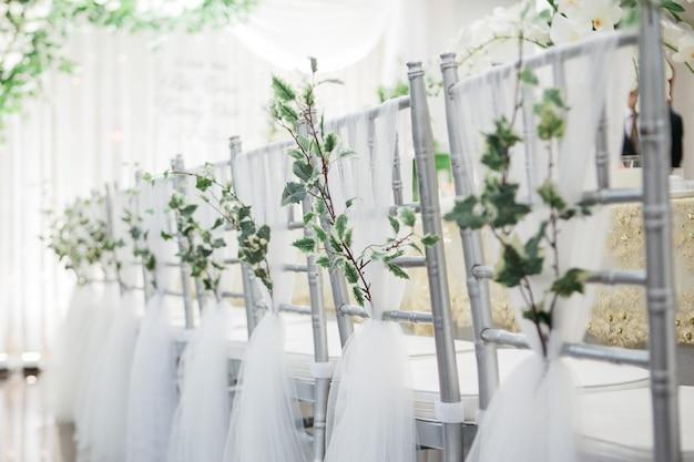 Flacher fokussierter schuss von schönen silbernen stühlen, die für eine hochzeit nahe einem hochzeitstisch verziert werden