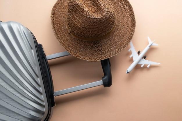 Flacher grauer koffer mit braunem hut und miniflugzeug