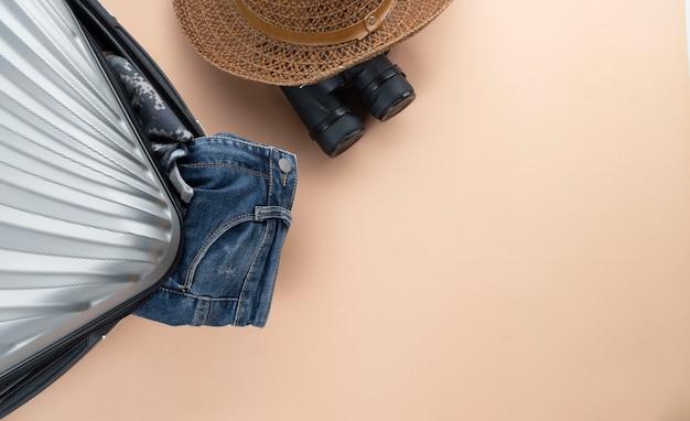 Flacher grauer koffer mit fernglas, hut und jeans