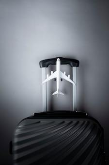 Flacher grauer koffer mit mini-flugzeug. reise-konzept