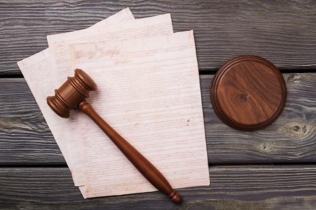 Flacher hammer und alte papiere. judgel hammer und papiere mit handschrift auf holzschreibtisch.
