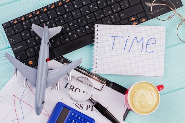Flacher heimbüroarbeitsplatz mit schwarzen tastaturbleistiftpapierblättern auf blauem hintergrund. wortzeit auf notizblock geschrieben.