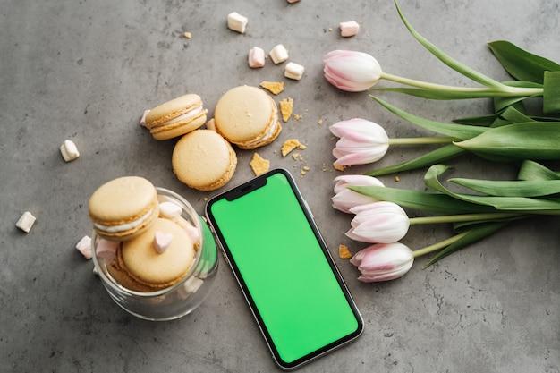 Flacher hintergrund von frischen tulpen, gelben französischen macarons und smartphone