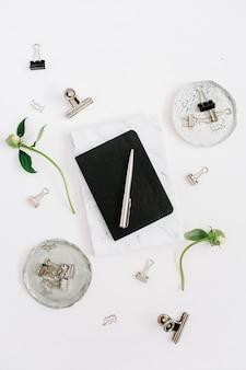 Flacher home-office-schreibtisch. arbeitsbereich mit schwarz- und marmortagebuch auf weiß