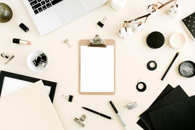 Flacher home-office-schreibtisch. arbeitsbereich mit zwischenablage, laptop auf pastellbeigem hintergrund. ansicht von oben