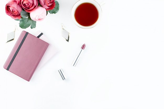 Flacher home-office-schreibtisch. femininer arbeitsbereich mit tagebuch, blumen, süßigkeiten, modeaccessoires. modeblogger-konzept.