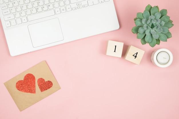 Flacher home-office-schreibtisch. frauenarbeitsplatz mit laptop, kosmetik, parfüm, zubehör auf rosa oberfläche. liebesbriefumschlag, rotes herz des valentinsgrußes