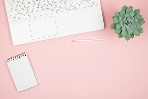 Flacher home-office-schreibtisch. frauenarbeitsplatz mit laptop, notizbuch, stift auf rosa oberfläche. draufsicht weibliche oberfläche.