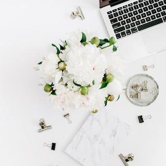 Flacher home-office-schreibtisch. frauenarbeitsplatz mit laptop, weißer pfingstrosenblumenstrauß, zubehör, marmortagebuch auf weiß