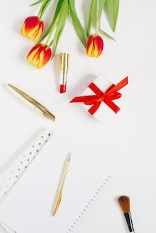 Flacher home-office-schreibtisch. frauenarbeitsplatz mit notizbuch, kosmetik, rotgelber tulpe, kosmetik auf weißem tisch.