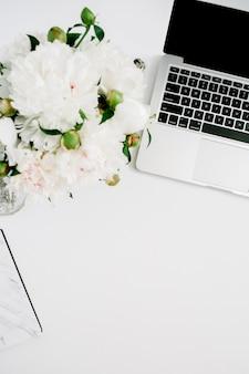 Flacher home-office-schreibtisch. weiblicher arbeitsbereich mit laptop, blumenstrauß der weißen pfingstrose, zubehör, marmortagebuch auf weiß
