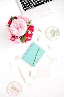 Flacher home-office-schreibtisch. weiblicher arbeitsbereich mit laptop, rosa und rotem rosenstrauß, goldenem zubehör, minztagebuch auf weiß