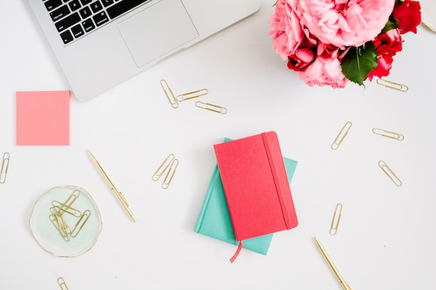 Flacher home-office-schreibtisch. weiblicher arbeitsbereich mit laptop, rosa und rotem rosenstrauß, goldenen accessoires, rotem und neuwertigem tagebuch auf weiß