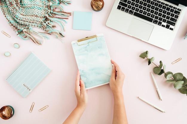 Flacher home-office-schreibtisch. weiblicher arbeitsplatz mit zwischenablage, laptop auf rosa hintergrund. ansicht von oben