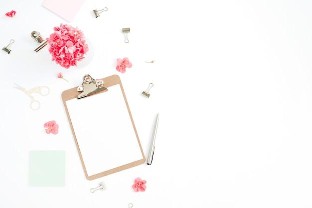 Flacher home-office-schreibtisch. zwischenablage mit kopierraum für text, rote blumen, accessoires, minztagebuch auf weiß
